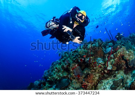 SCUBA diver with an advanced Closed Circuit Rebreather explores a deep tropical coral reef - stock photo