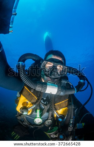 SCUBA diver with an advanced closed circuit rebreather underneath a boat - stock photo