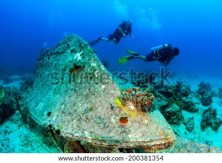 SCUBA divers around an upturned underwater wreck - stock photo