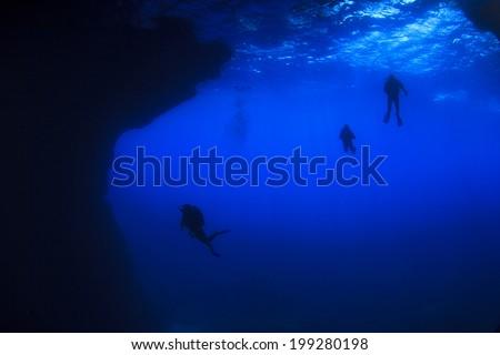 Scuba divers enter underwater cave - stock photo