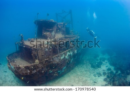 SCUBA Divers explore an underwater shipwreck - stock photo