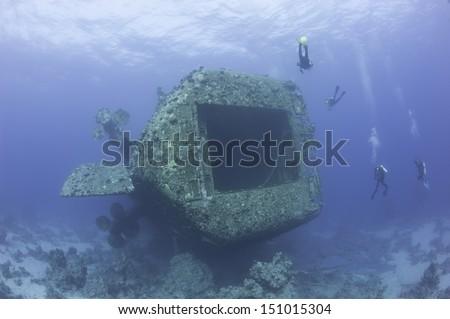Scuba divers exploring a large sunken underwater shipwreck - stock photo