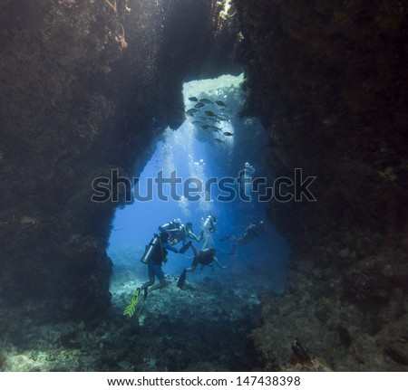 Scuba divers exploring an underwater sea cave in a tropical coral reef - stock photo