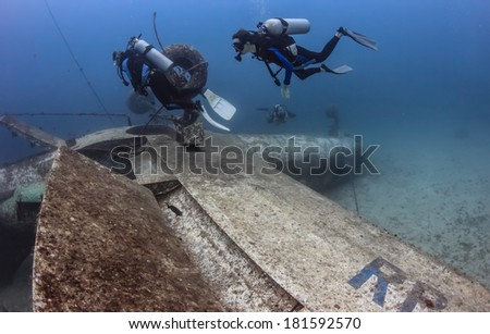 SCUBA divers over the wing of an upside down aircraft wreck on the seabed - stock photo