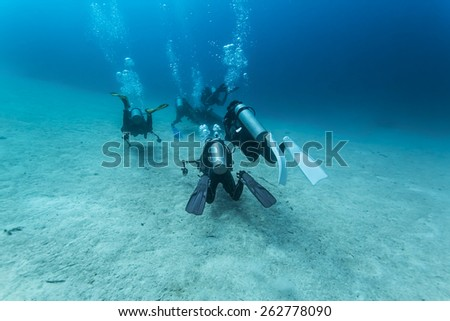 Scuba Divers passing through sandy bottom tropical sea