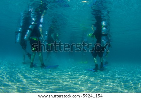 Scuba divers standing in shallow water prior to a beach dive.