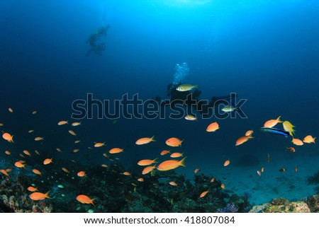 Scuba divers swim over coral reef underwater in ocean