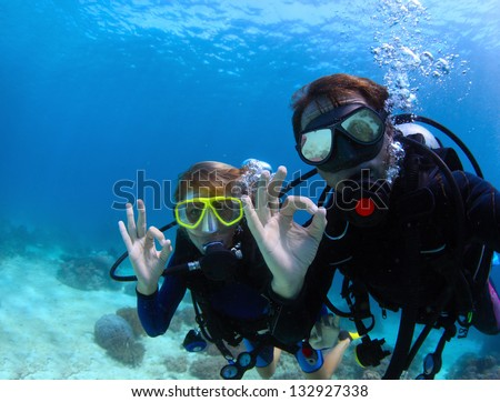 Scuba divers underwater showing ok signal - stock photo