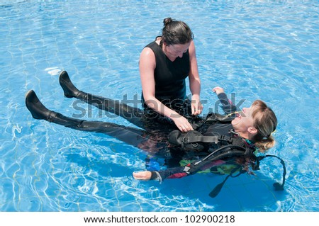 Scuba diving instructor and student having fun  in a swimming pool - stock photo