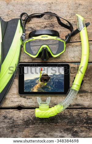 Scuba diving or snorkelling lesson template mock-up background. Flippers, mask, snorkel with blank tablet PC on wood background - stock photo