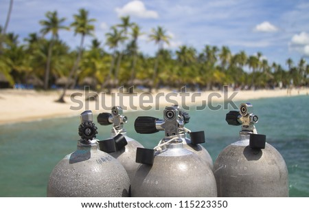 Scuba diving tanks with blue ocean and palm tree background. - stock photo