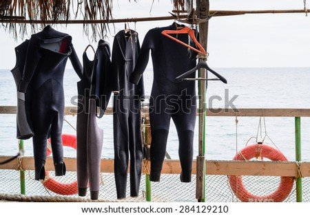 Scuba Diving Wet Suits Hanging to Dry on Rail on Deck of Boat with View of Ocean in Background - stock photo