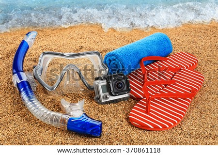 Scuba mask and snorkel on the sand. Action camera and flip-flops. - stock photo