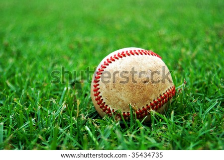 Scuffed old baseball on the grass - stock photo