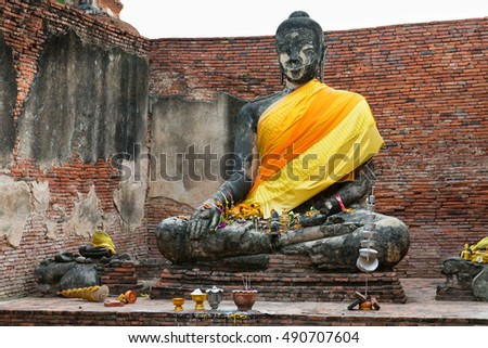 Sculpted, stone image of the Buddha in a seated position, dressed in yellow robes at Wat Thammikarat in Ayutthaya, Thailand.