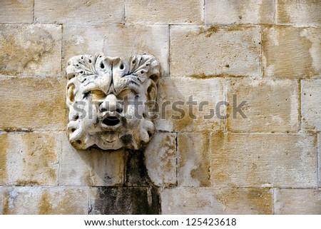 Sculpted stone mask figure on ancient fountain on the side of Church of Saint Blaise (St.Vlaha) Dubrovnik, Croatia - stock photo