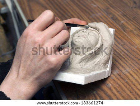 Sculptor Modeling clay models in workshop. - stock photo