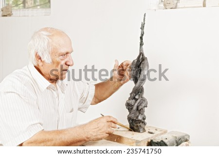 Sculptor tells about his sculpture in a workshop - stock photo