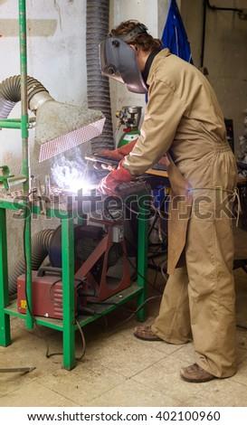 Sculptor welding a metal piece - stock photo