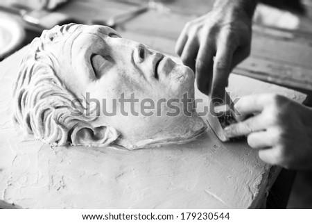 Sculptor working on head sculpture - stock photo