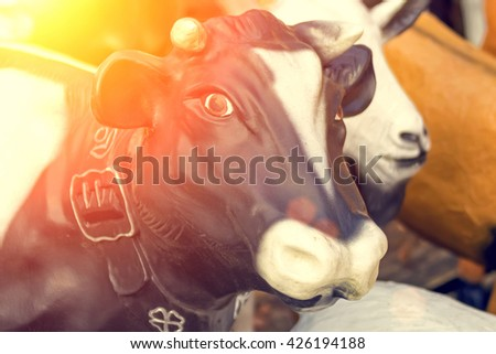 Sculpture black and white cow, sunshine. Toned - stock photo