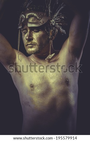 Sculpture, Man with body painted gold feather mask and steel sword - stock photo