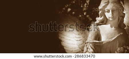 sculpture of a beautiful angel on  dark background (details)