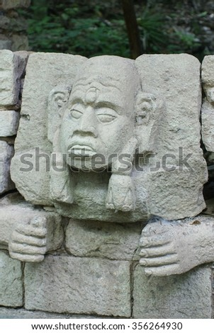 Sculpture of a Mayan face and hands in the side of a temple in Copan - stock photo