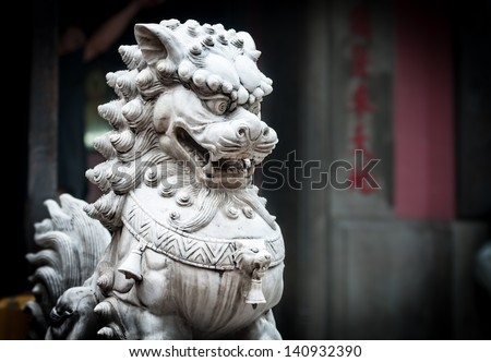 Sculpture of dragon with furious face in buddhist temple, gray wall with characters in background. White stone statue of animal in anger. Traditional asian art and symbol. - stock photo