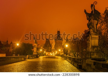 Sculpture of St. Augustine with a burning heart in hand trampling heretical books of Charles Bridge in Prague (Czech Republic) at night lighting. Long exposure. - stock photo
