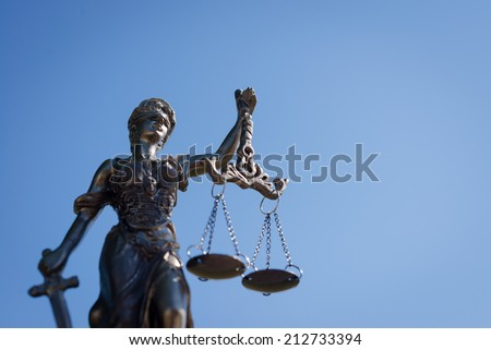 sculpture of themis, femida or justice goddess on bright blue sky background - stock photo