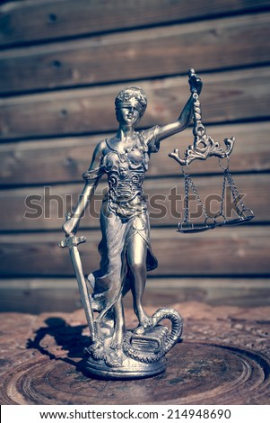 sculpture of themis, femida or justice goddess on wood lining copyspace background - stock photo