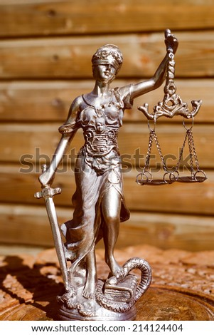 sculpture of themis, femida or lady justice goddess on wood lining copy space background - stock photo