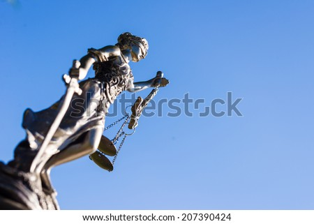 sculpture of themis greek goddess symbol of justice on blue sky copy space background - stock photo