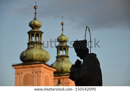 Sculpture priest with Bible in sunshine Klodzk Poland - stock photo