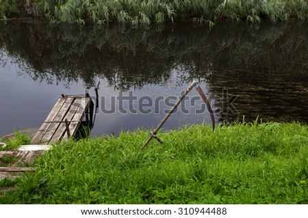scythe on the riverbank and grass reflection - stock photo