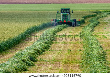 SDE YOAV, ISRAEL - MARCH 21, 2009: Harvester harvests wheat  on the field of Sde Yoav kibbutz. First kibbutz was established in 1909 and it is collective community traditionally based on agriculture. - stock photo
