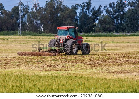 SDE YOAV, ISRAEL - MARCH 21, 2009: Tractor plowing the agricultural field of Sde Yoav kibbutz. First kibbutz was established in 1909 and it is collective community traditionally based on agriculture. - stock photo
