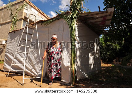 SDEROT, ISR - OCT 10:Israeli woman coming out from a sukkah on Oct 10 2008.Sukkot is one of three festivals each year during which the Israelites made a pilgrimage to the Temple in Jerusalem