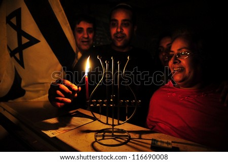 SDEROT, ISRAEL -DECEMBER 21 2008:Israeli family lights the first candles of the Jewish holiday Hanukkah in Sderot Israel.It commemorates the rededication of the second Jewish Temple in Jerusalem - stock photo