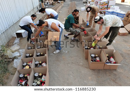 SDEROT - SEPTEMBER 15:Member of Chabad is giving food to poor Jewish families on September 15 2008 in Sderot,Israel.Chabad is an educational organization dedicated to help every Jew in the world. - stock photo