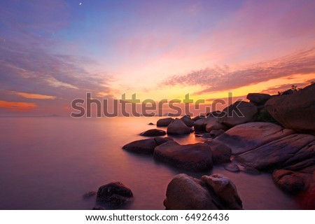 Sea and rock at the sunset. Nature composition under long exposure. - stock photo