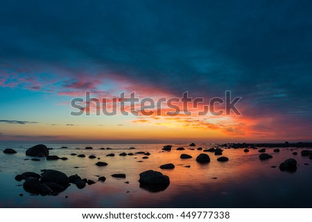 Sea and rocks with sunset sky. - stock photo