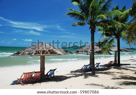Sea and Sand  against Blue Sky with Beach chairs and Palm Trees