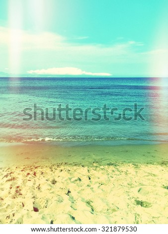 Sea and sand beach. Retro styled image with light leaks. - stock photo