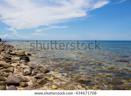 Sea and stones summer vacation travel photo. Tropic island stone beach in sunny day. Calm and clear sea water over stone. Blue cloudy sky with horizon line. Sea landscape of exotic island. Philippines - stock photo