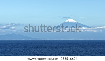 Sea approach to Shimizu, Japan with the sunlit snow capped peak of Mt. Fuji gleaming in the background above the low lying clouds - stock photo
