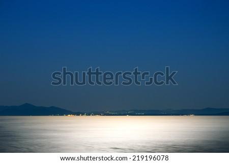 Sea at night illuminated by the moonlight  - stock photo