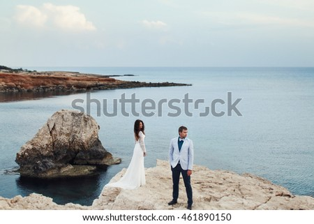 Sea azure surrounds a wedding couple standing on the rock