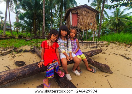 Sea Bajau children posing in front of their traditional house. Shallow dof, selective focus on the face of the children. - stock photo
